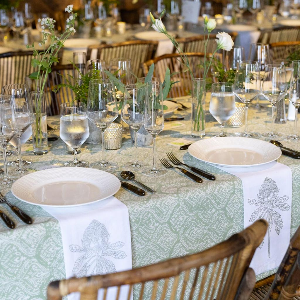 New Hampshire barn wedding, detailed view of place setting on a green tablecloth with white plates
