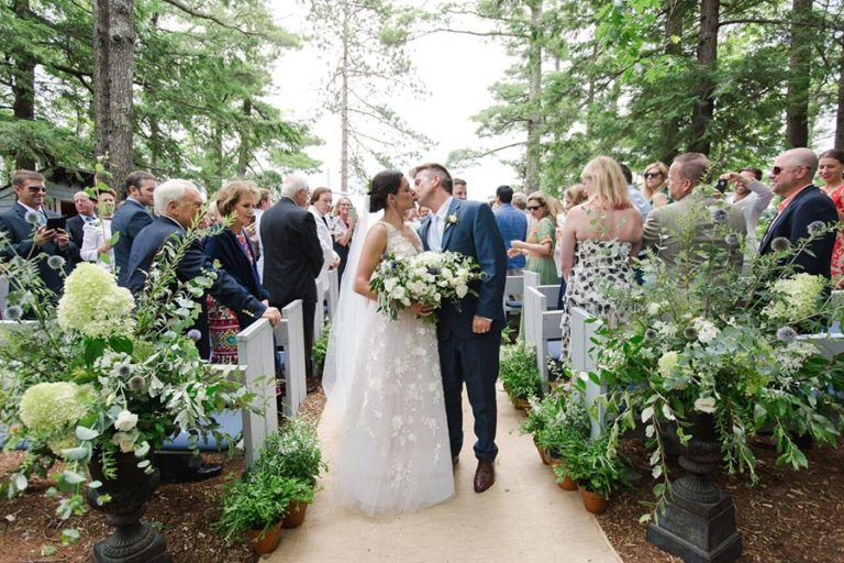 Wedding on island on Squam Lake, NH. Bride and groom kissing with guests looking on